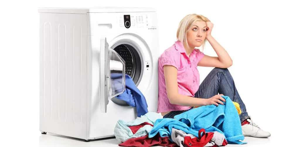 imagem de mulher aborrecida, com sua máquina de lavar quebradaimagem de mulher aborrecida, com sua máquina de lavar quebrada